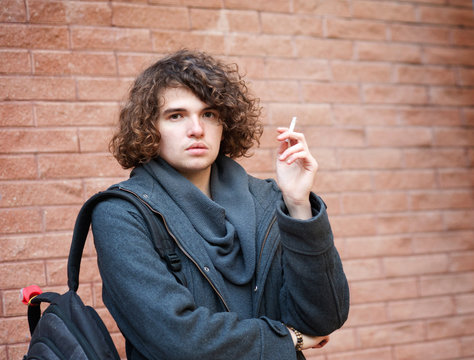 Portrait of a handsome man standing against brick wall and smoking a cigarette.