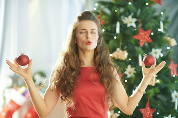 smiling trendy woman near Christmas tree doing yoga