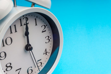 Clock on blue background with selective focus and crop fragment. Copy space concept