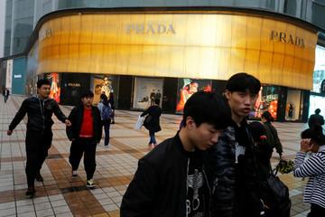 People walk past a Prada luxury fashion boutique near Wangfujing Street
