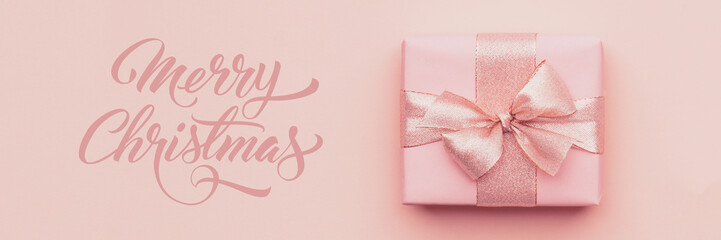 Christmas banner. Beautiful pink christmas gift isolated on pastel pink paper background.