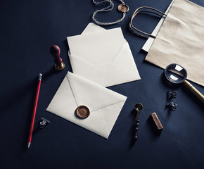 Blank envelopes with wax seal, stamp and vintage stationery on black paper background.