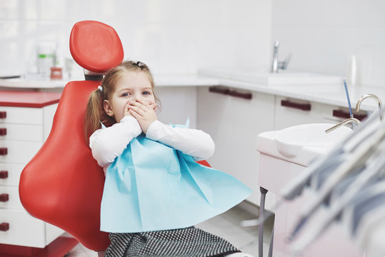 Frightened little girl at dentist office covered mouth with hands