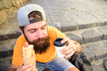 Tasty sausage in roasty bun. Urban food culture concept. Hipster eat hot dog while sit on stairs outdoors. Hipster enjoy hot dog and drink paper cup. Man bearded enjoy street food urban background