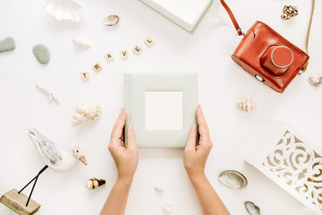 Woman hands hold photo album. Retro camera, bird sculpture on white background. Flat lay, top view travel mockup.