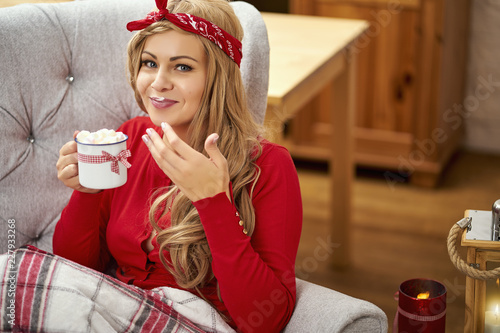 Young Smiling Beautiful Woman In Armchair With A Cup Of Hot