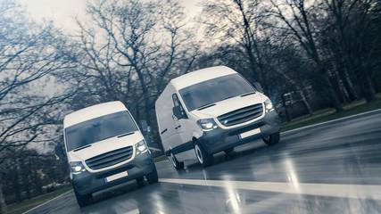 Zwei weiße Transporter fahren schnell auf einer nassen Straße