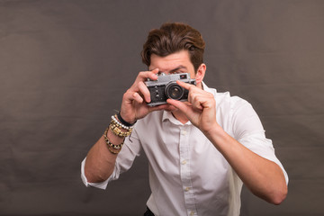 People, photographer and vintage concept - man searching for an interesting subject for his photo holding a vintage camera on brown background