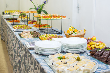 Buffet table of reception with cold snacks, meat and cakes