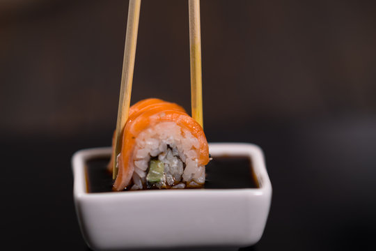 Person dipping a fresh sushi roll in soy sauce