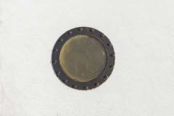 Sailboat porthole in white grunge metal wall