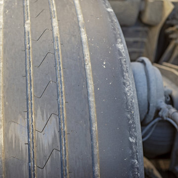 Worn out tire of heavy vehicle. Close up view
