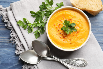 Flat lay composition with delicious pumpkin cream soup in bowl on wooden background