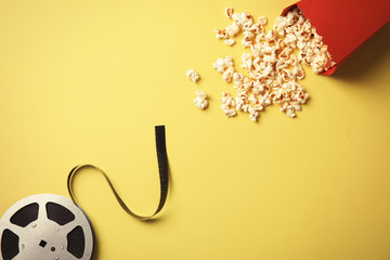Tasty popcorn and film reel on color background, top view. Cinema snack