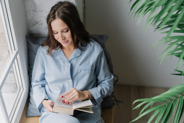 Top view of pleased woman with dark long hair, focused into book, reads something exciting, enjoys cozy atmosphere at home, poses on window sill in empty room. Its time for reading and rest.