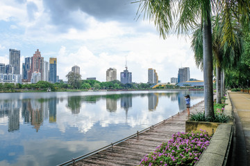 Female photographer taking photos of downtown bangkok across the lake