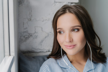 Headshot of attractive female meloman enjoys music in earphones with high volume, likes peaceful atmosphere, looks thoughtfully at window, listens favourite song. People, rest, technology concept