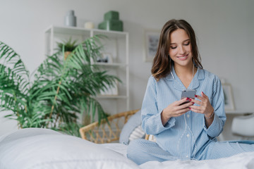 Happy woman with appealing look, holds modern cell phone, downloads song to playlist, listens music with earphones, sits crossed legs on comfortable bed, has charming smile on face, uses free wifi