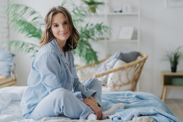 Indoor shot of pretty dark haired woman sits crossed legs on bed, dressed in nighclothes, white socks, looks direcltly at camera, feels relaxed while listens calm music in earphones. Rest and day off