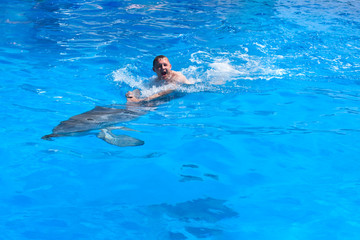 A young man is riding dolphin, boy swimming with dolphin in blue water in water pool, sea, ocean, dolphin saves a man