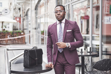 Young businessman with a briefcase near a beautiful office. Business meeting