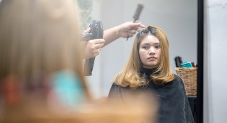Women are blowing hair at hair salon.