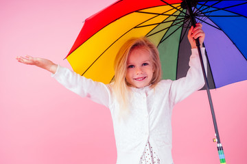 portrait of happy and beautiful little blonde girl blue eyes in white dress in peas holding a colorful rainbow umbrella autumnal springtime season in the studio on a pink background.charming child