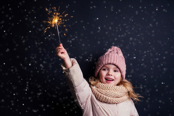 charming little girl in a knitted pink hat holding fireworks on black background in a studio.Cute...