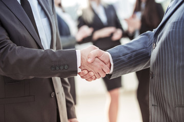 concept of cooperation - handshake of business partners on the background of the employees in the office