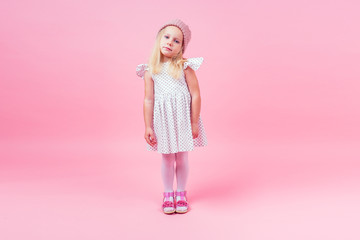 Full body portrait of adorable little girl blonde girl blue eyes model in beige knitted pink hat in white princess dress in peas autumnal springtime season in studio shot on pink background