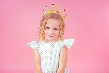 little girl beauty queen blue eyes, curls blonde hairstyle with a tiara crown on her head in a cute white dress in peas posing in the studio on a pink background.birthday celebration,Beauty contest