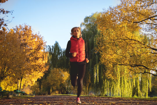 Image of woman runner in warm clothes and earphones running in autumn park