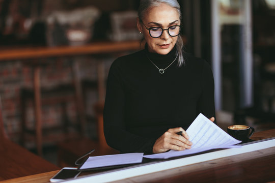 Mature businesswoman reading some paperwork at cafe