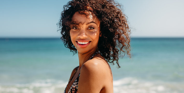 Portrait of a curly haired woman at the beach