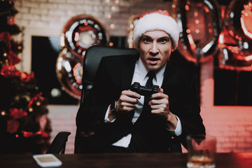 Businessman Playing on Console on New Year Eve.