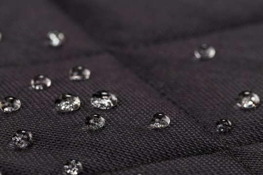 Water drops on waterproof black fabric