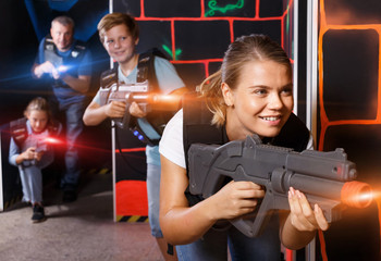 Happy young girl with laser gun  during laser tag game with  pla