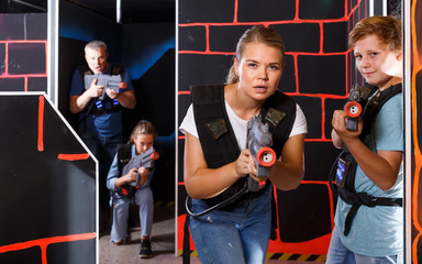 Happy teen boy having fun on laser tag arena with his older sister