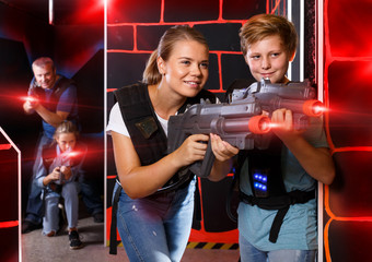 teen boy having fun on laser tag arena with his older sister