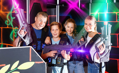 Group of happy teenagers and adults with laser guns posing toget