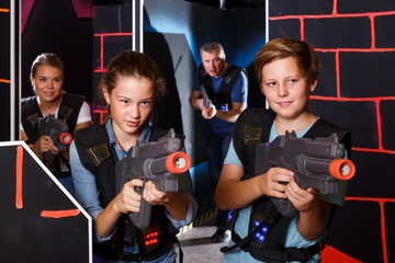 teen brother and sister with laser pistols playing laser tag with their parents