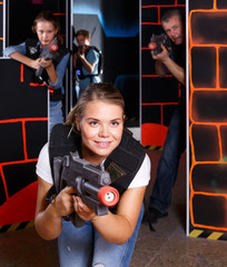 positive girl with laser pistol playing laser tag with friends
