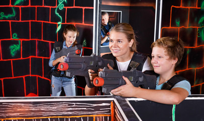 Mother and son with laser pistols playing laser tag