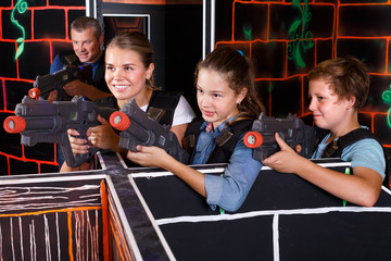 Smiling boy and girls aiming laser guns and playing laser tag game with parents