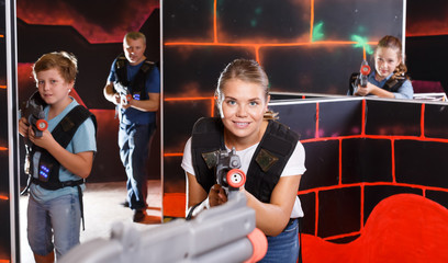 Excited girl aiming laser gun near other players during laser tag game