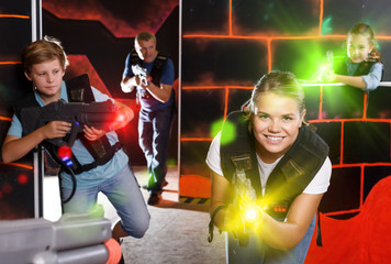 Children and parents aiming laser guns  during lasertag game in