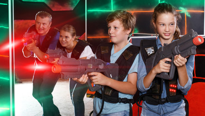Smiling kids and  parents with laser guns and playing together l