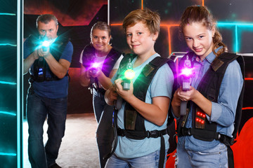 interested teen brother and sister with laser pistols playing la