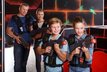 Happy boy and girl posing with laser guns