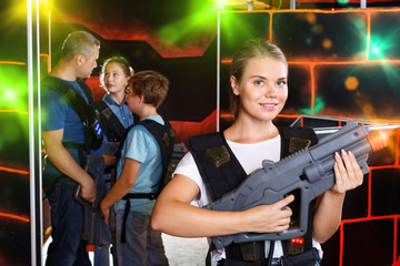 Cheerful young woman posing with laser pistol while playing with